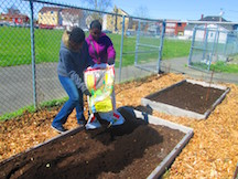 two girls pouring soil into raised bed at barnum garden