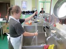student washing utensils