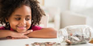 child looking at a jar of money
