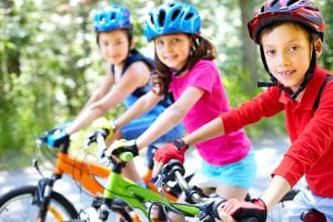 three children in helmets on bikes