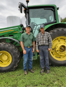 Chris and Todd Hannan in front of a John Deere tractor