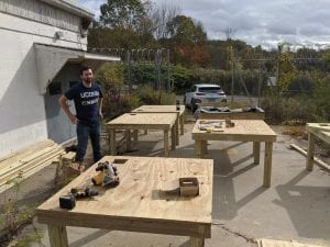 Greg standing behind wooden tables during a summer project for his internship