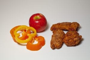 fried chicken next to peppers and an apple