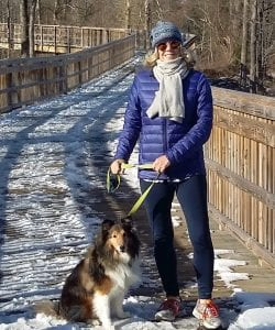 woman walking a dog on the Still River Greenway in Brookfield