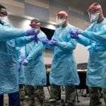 Florida National Guard members putting personal protective equipment on