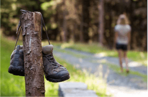 hiking boots hanging on fence post and person walking down the trail in the distance