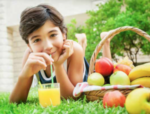 girl sitting in grass drinking orange juice out of straw with basket of fruits and vegetables next to her